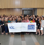 Group of females in HVAC industry holding giant TCC banner